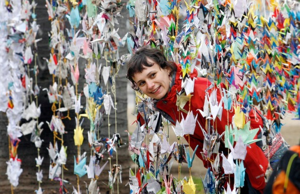 A woman looks at origami cranes in Valparaiso city